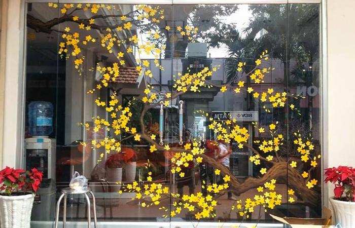 Chọn các họa tiết quen thuộc như hoa Mai trang trí trên cửa kính văn phòng